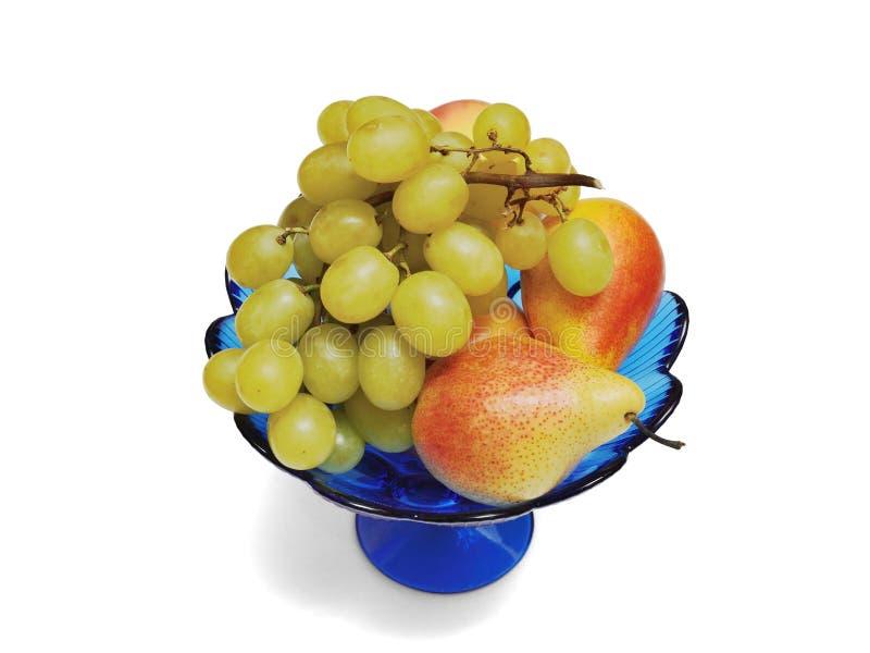 Vase vom blauen Glas mit der Frucht lokalisiert auf einem weißen Hintergrund lizenzfreies stockbild