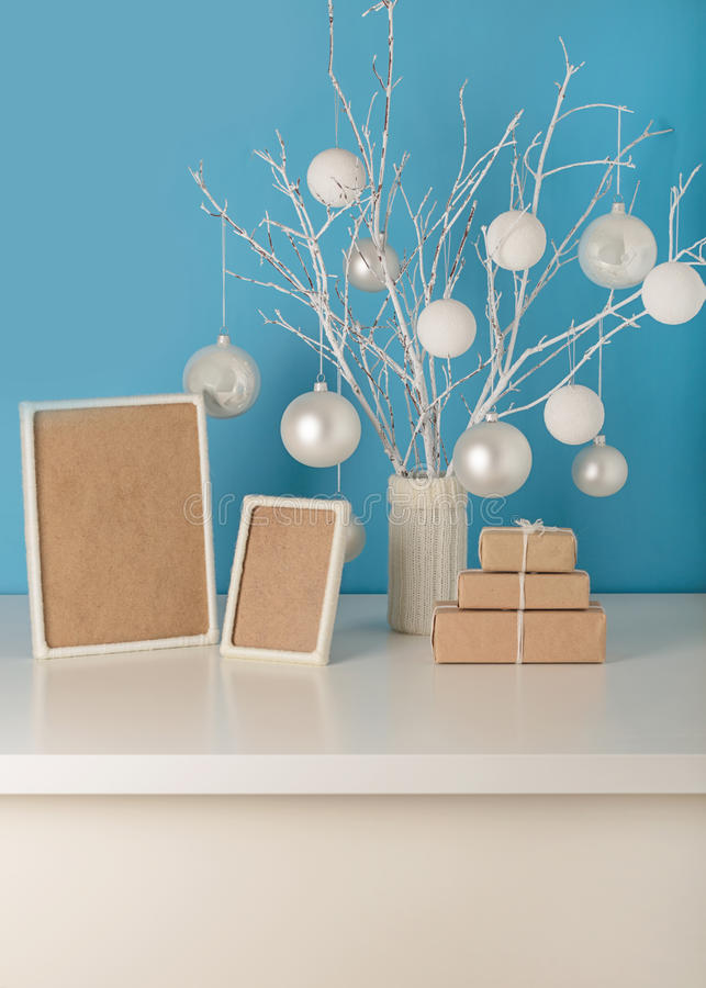 Vase in white knitted cover with white branches and Christmas to. Ys. Empty wooden frame decorated with white yarn. Gifts are Packed in Kraft paper royalty free stock image