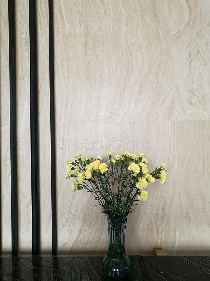 Vase of yellow carnation flower in the center of marble bar in the hotel lobby with blur background. For decoration royalty free stock photography