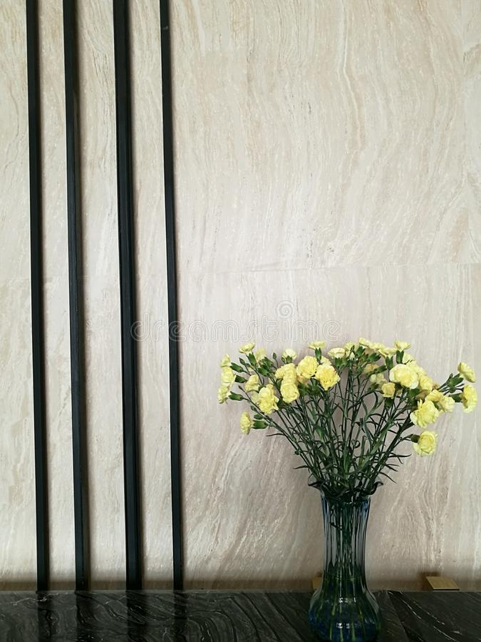 Vase of yellow carnation flower in the right side of marble bar in the hotel lobby with blur background, hotel decoration. Vase of yellow carnation flower in the royalty free stock photos