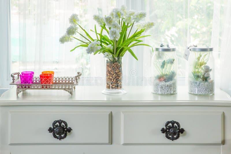 Vasen med blomman och tappning dekorerar på tabellen med fönsterbräda I royaltyfri foto