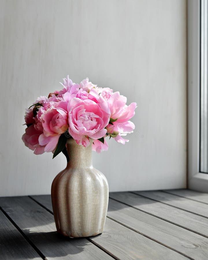 Vasen med den h?rliga pionen blommar p? f?nsterbr?da arkivbilder