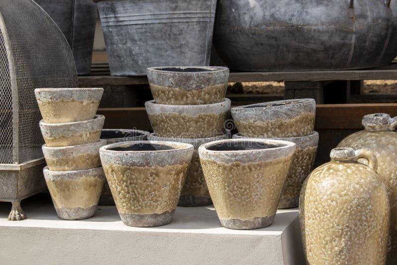 Vasi da fiori dell'argilla nella finestra di un negozio di giardinaggio Brown ha lustrato i vasi per i fiori della stanza e la de fotografia stock