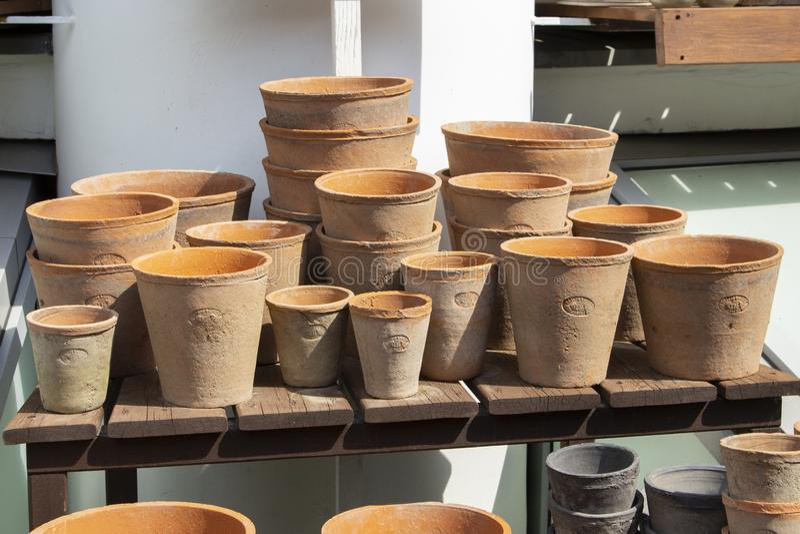Vasi da fiori di argilla rossa, contenitore per i fiori crescenti Molto gruppo di vasi di argilla, finestra del negozio di fiore, fotografie stock
