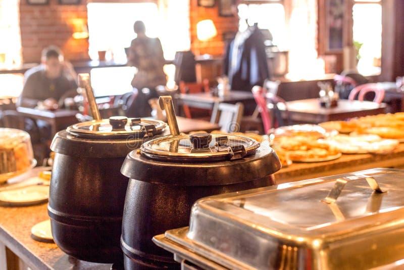 Vasi heated della minestra con la siviera in caffè fotografia stock