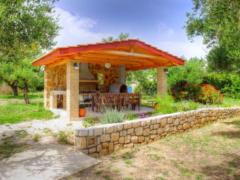 VASILIKOS,扎金索斯州海岛,希腊, 2016年5月30日:在夏天亭子的美丽的景色有BBQ烤肉的壁炉的在希腊语旁边 库存图片