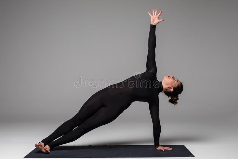 Vasishthasana. Beautiful yoga woman practice yoga poses on grey background. Yoga concept stock image