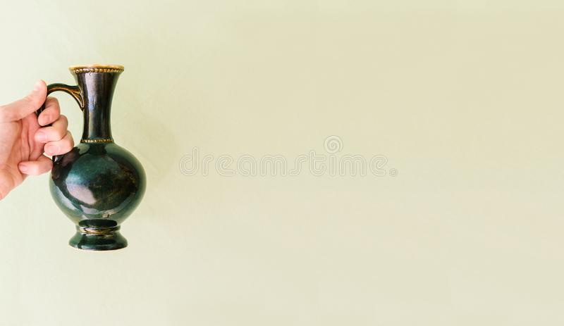 Vaso antigo na mão de uma mulher Uma mulher guarda uma antiguidade em um fundo verde Lugar para o texto fotografia de stock royalty free