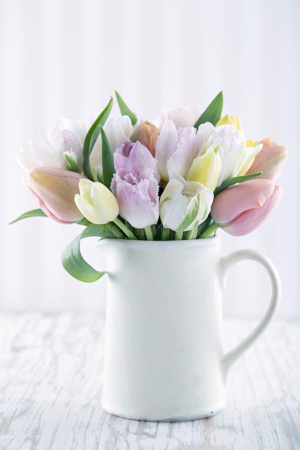 Vaso branco com tulipas coloridas fotografia de stock