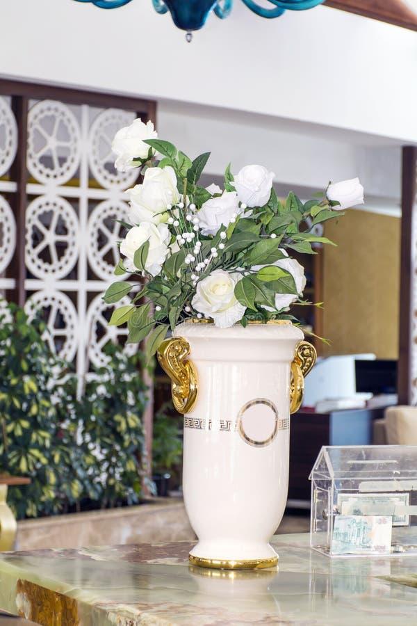 Vaso cerâmico branco grande com as rosas artificiais brancas imagens de stock royalty free