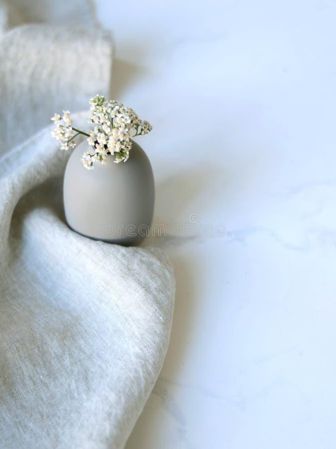vaso cinzento com wildflowers em um fundo branco imagem de stock