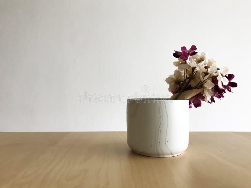 Vaso com as flores na tabela de madeira e no fundo branco da parede fotografia de stock royalty free