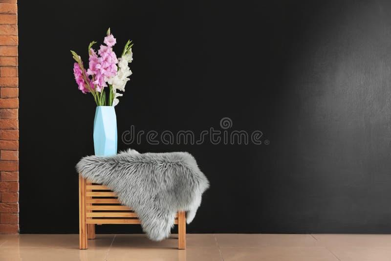 Vaso con i bei fiori di gladiolo sulla tavola vicino alla parete scura all'interno fotografie stock