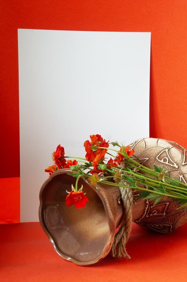 Vaso con i fiori e una foglia bianca immagine stock libera da diritti