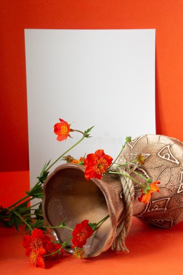 Vaso con i fiori e una foglia bianca fotografia stock