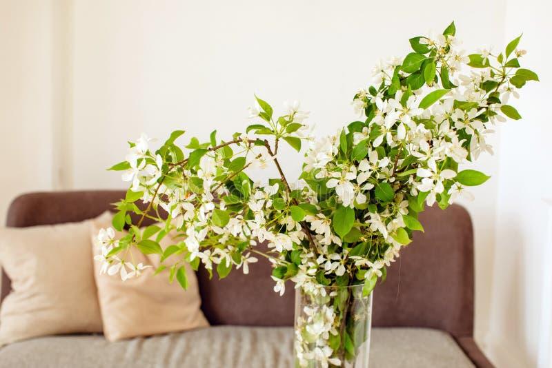 Vaso con i fiori vicino al sofà immagini stock