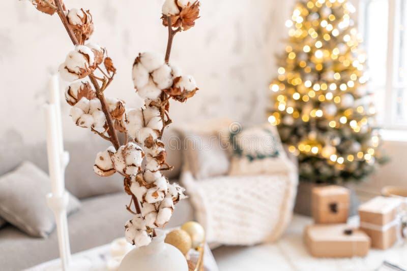 Vaso con i rami del cotone Salone leggero con l'albero di Natale Sofà comodo, alto grande Windows fotografia stock