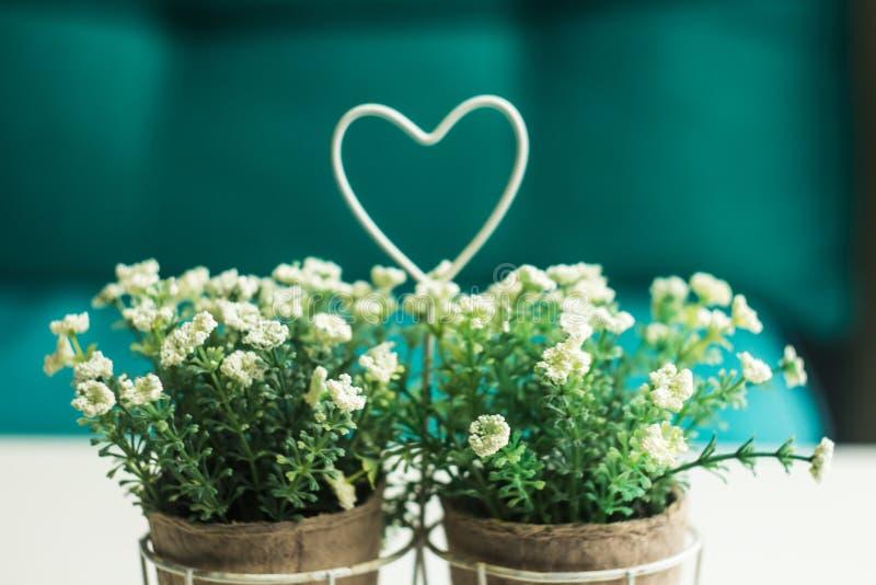Vaso con i wildflowers e cuore sulla tavola immagini stock libere da diritti