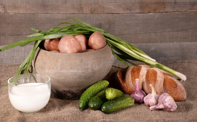 Vaso con le patate, il latte e le verdure immagini stock libere da diritti