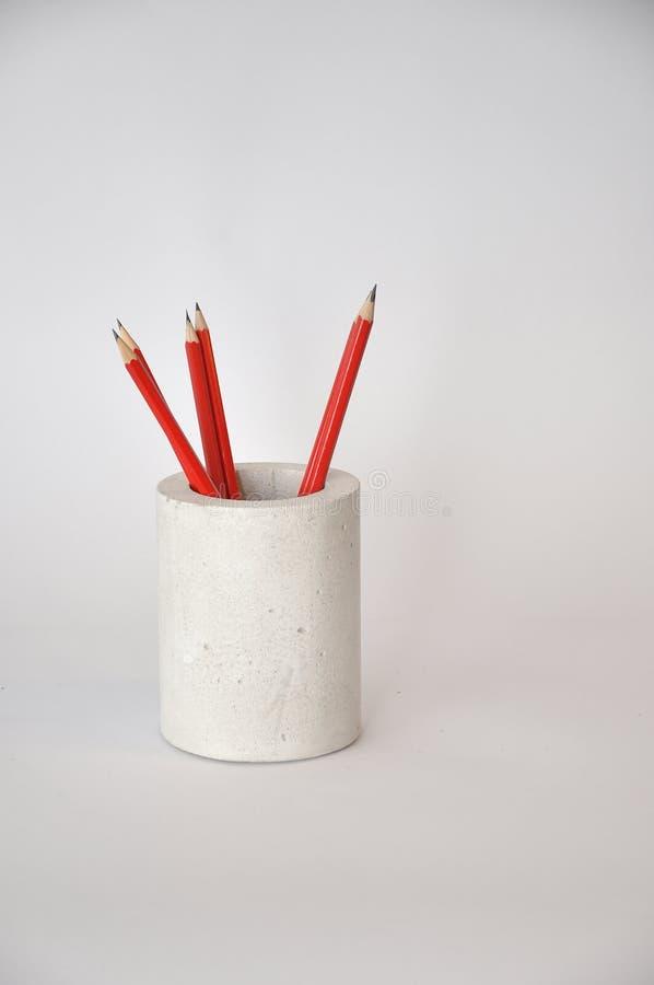Vaso concreto con le matite rosse fotografie stock
