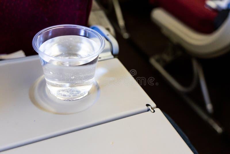 Vaso de agua de aviones de la cabina en la tabla Bebida para prevenir la deshidratación fotografía de archivo libre de regalías