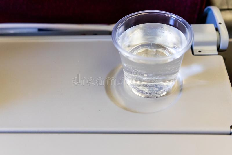 Vaso de agua de aviones de la cabina en la tabla Bebida para prevenir la deshidratación imagenes de archivo