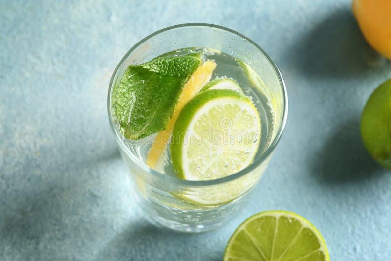 Vaso de agua con el limón y la cal en la tabla de color imagen de archivo libre de regalías