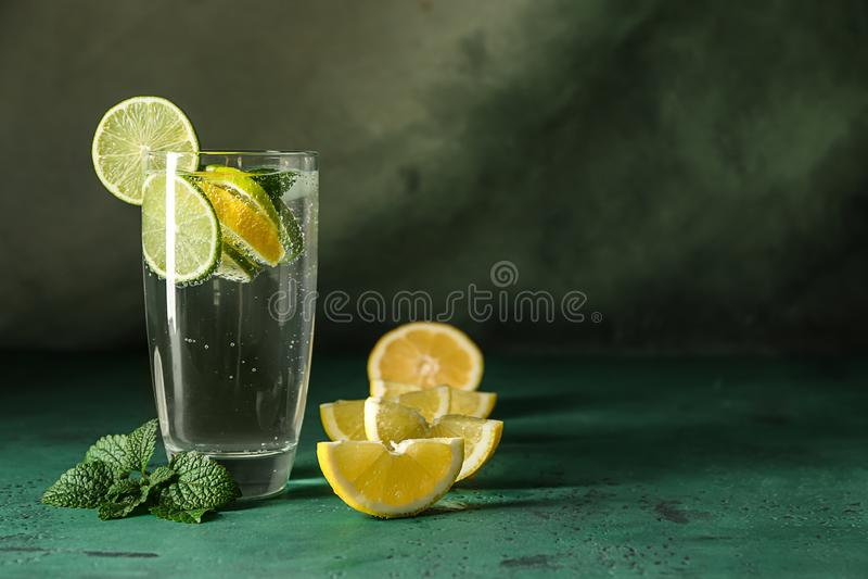 Vaso de agua con el limón y la cal en la tabla de color imagen de archivo