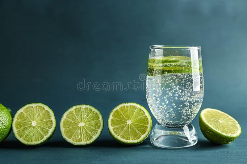Vaso de agua con la cal en fondo del color imagenes de archivo