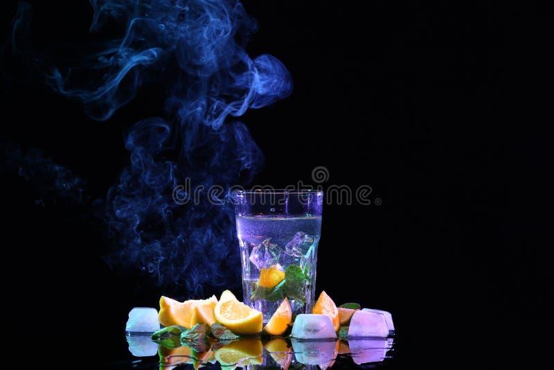 Vaso de agua con las hojas de menta, el limón cortado y los cubos de hielo en fondo negro fotografía de archivo