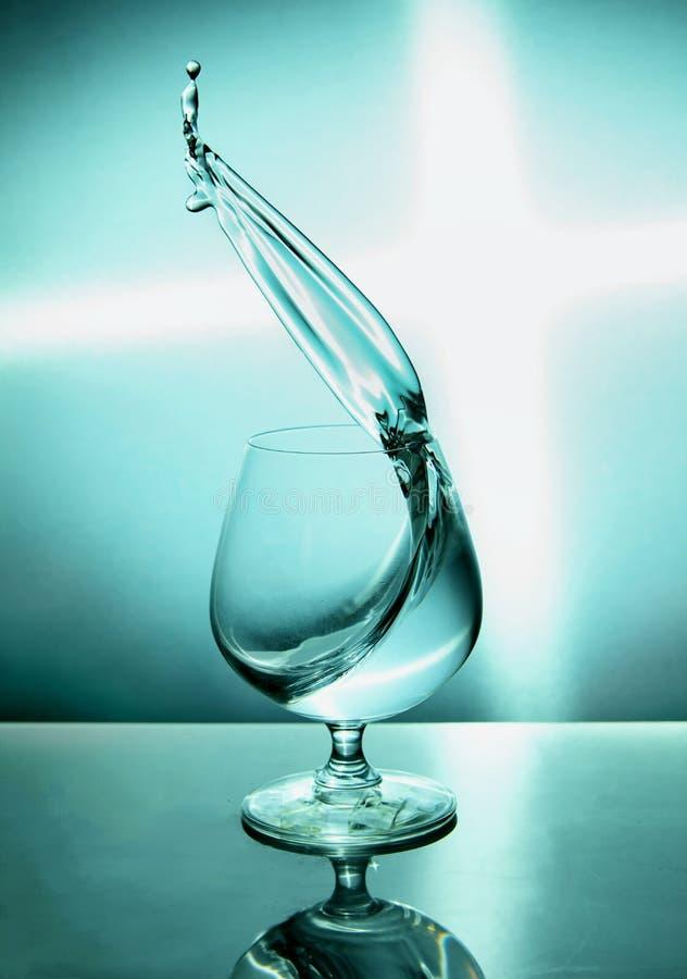 Vaso de agua con una onda en un fondo azul imágenes de archivo libres de regalías