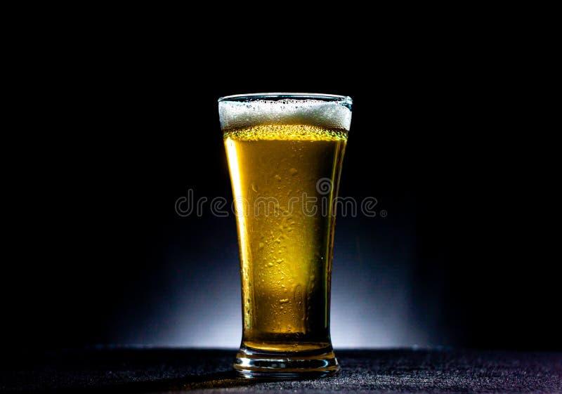 vaso de cerveza aislado en mesa negra imagen de archivo