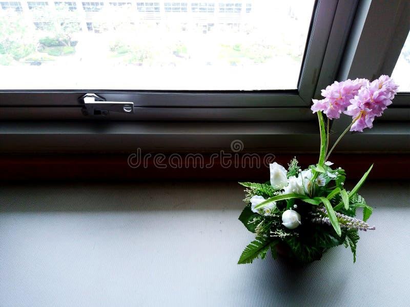 Vaso de flor bonito na tabela branca e colocação perto do assento de janela imagens de stock royalty free