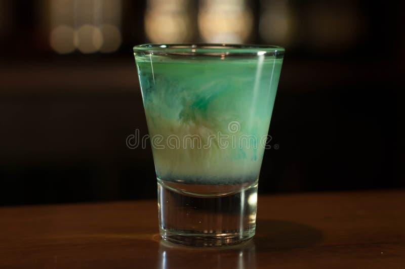 Vaso de medida con la bebida azul del alcohol en la tabla de madera en barra imagen de archivo