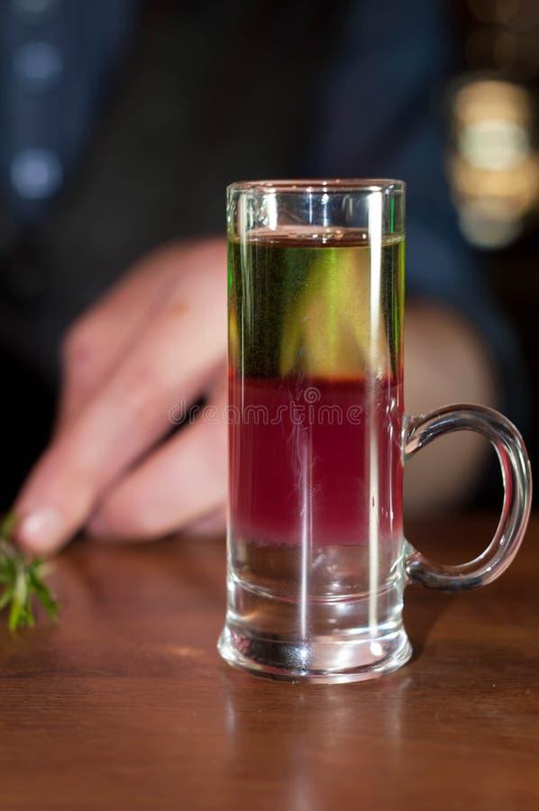 vaso de medida con la bebida del alcohol y romero en contador de madera imagenes de archivo