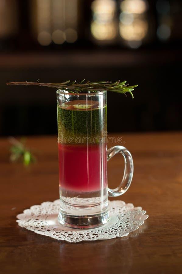 Vaso de medida con la bebida multicolora del alcohol y romero en la servilleta blanca foto de archivo