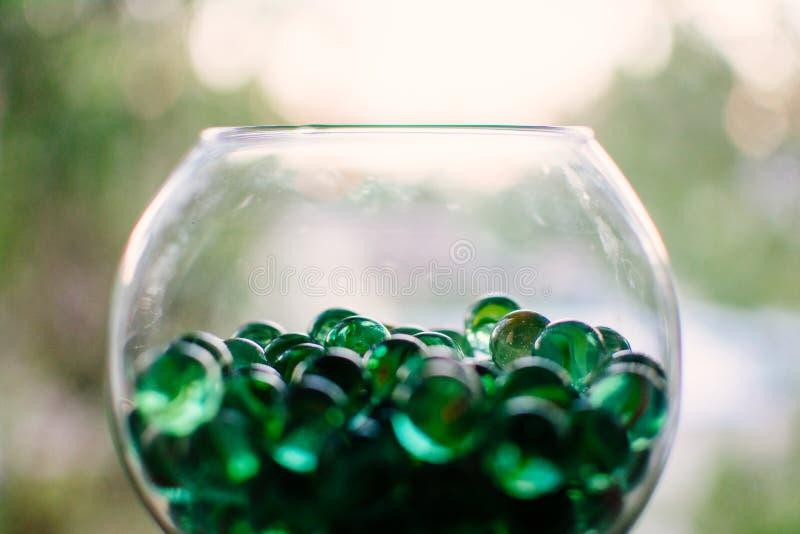 Vaso de vidro com bokeh verde dos mármores imagem de stock royalty free