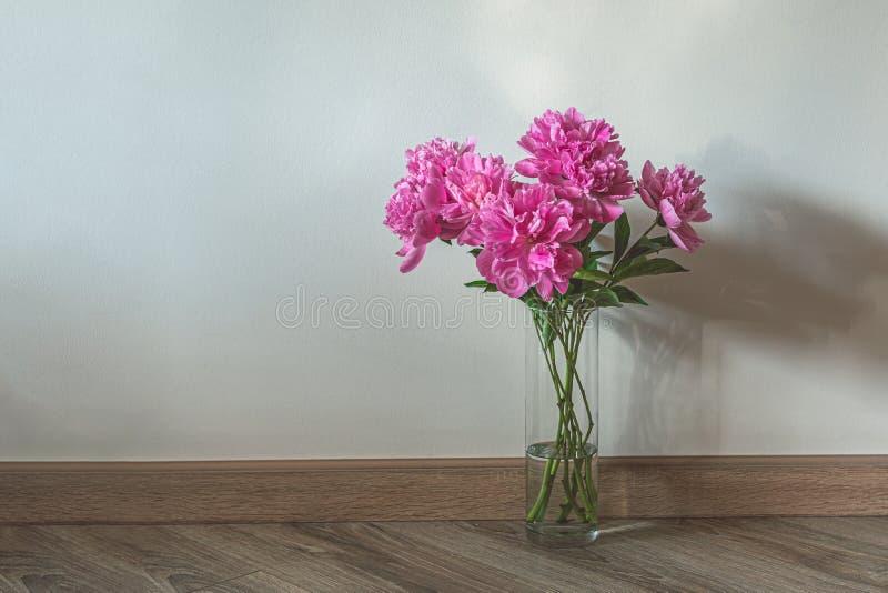Vaso de vidro com peões cor-de-rosa no chão de madeira fotografia de stock royalty free