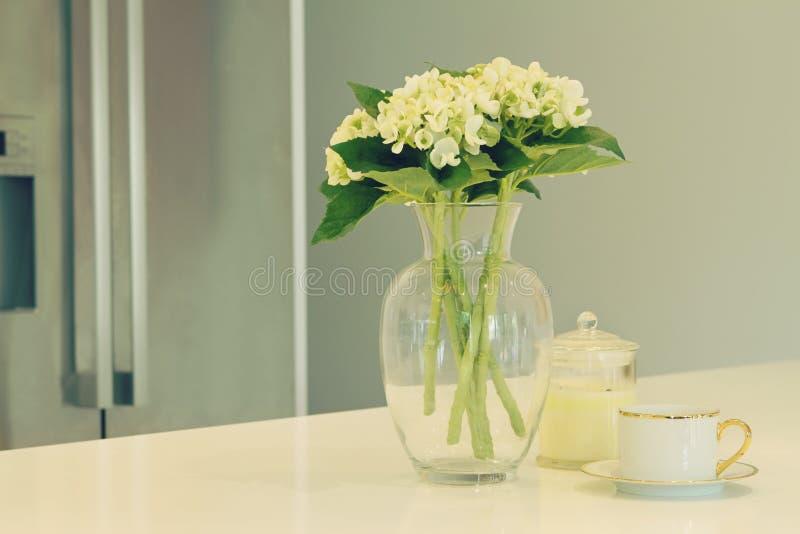 Vaso de vidro das flores brancas e da xícara de chá em uma cozinha com borrado imagem de stock royalty free