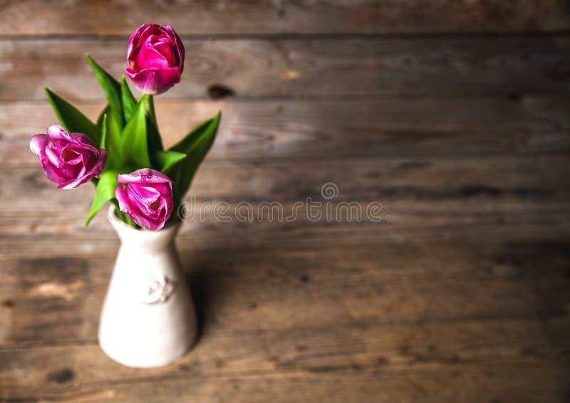 Vaso dei tulipani naturali Fiori su un fondo di legno fotografia stock