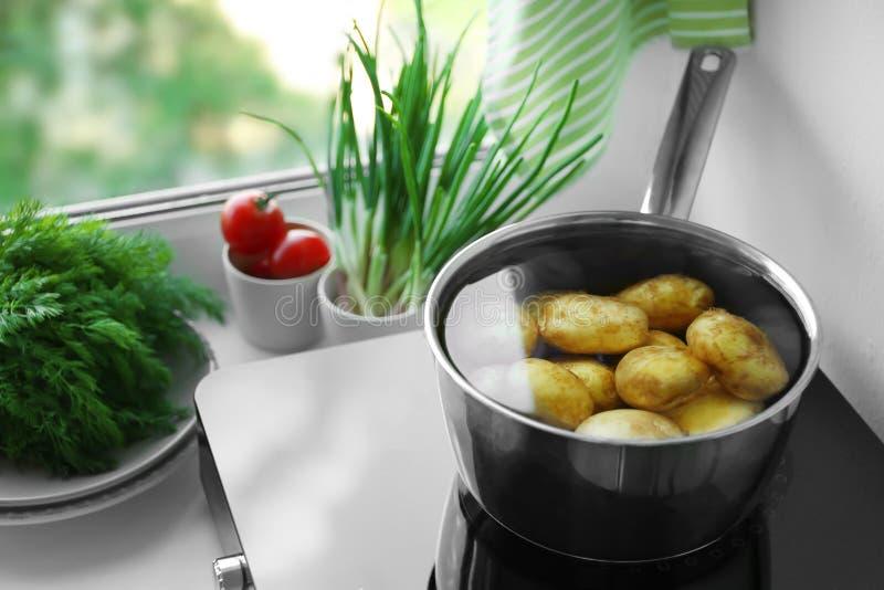 Vaso del metallo con la patata sul fornello di induzione immagine stock