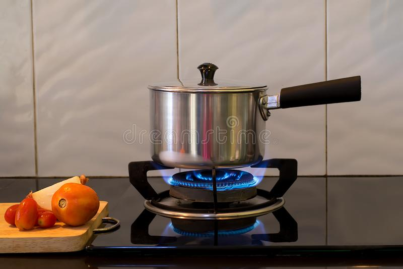 Vaso del metallo sulla stufa di gas della fiamma per la minestra dell'acqua bollente, fotografie stock
