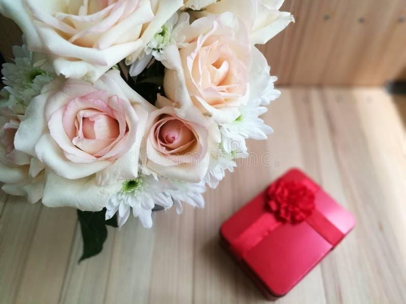 Vaso delle rose del mazzo in secchio di alluminio e contenitore di regalo rosso su fondo di legno fotografie stock