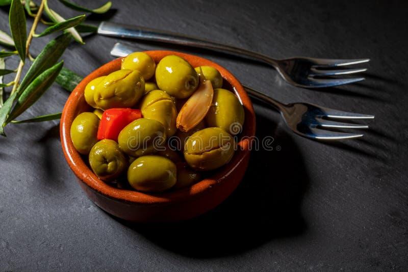 Vaso di argilla con le olive dell'artigiano immagine stock