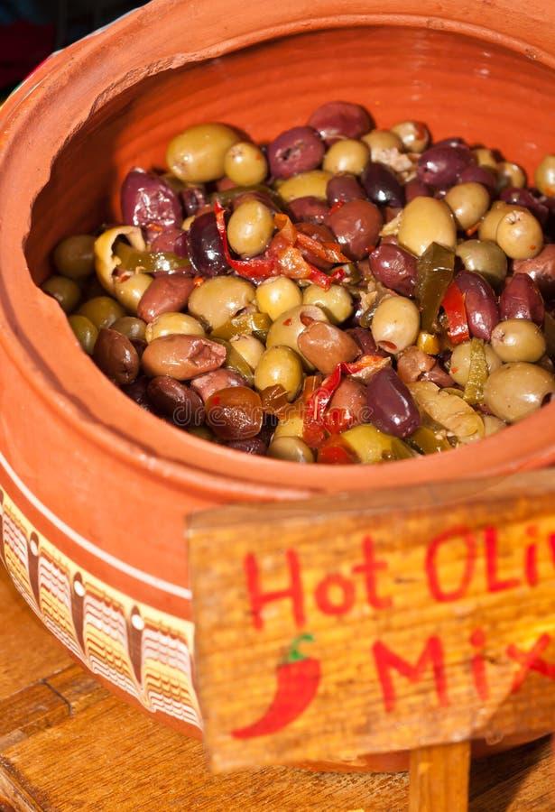 Vaso di argilla delle olive calde e miste in olio d'oliva su esposizione e per la vendita ad un mercato tropicale degli agricolto fotografia stock
