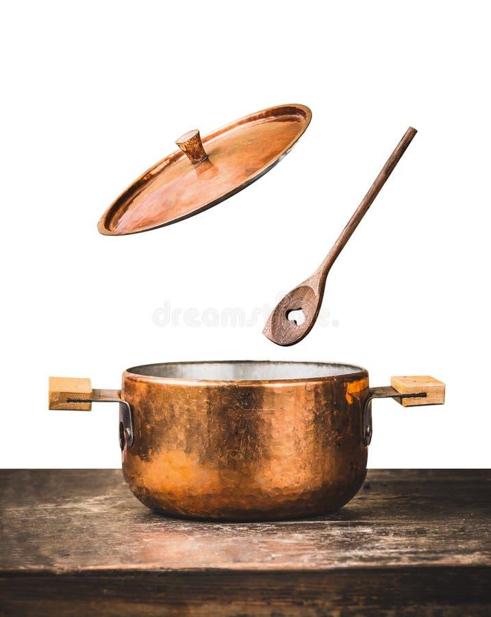 Vaso di cottura di rame con il coperchio aperto di volo ed il cucchiaio di legno sulla tavola, isolata su fondo bianco immagine stock