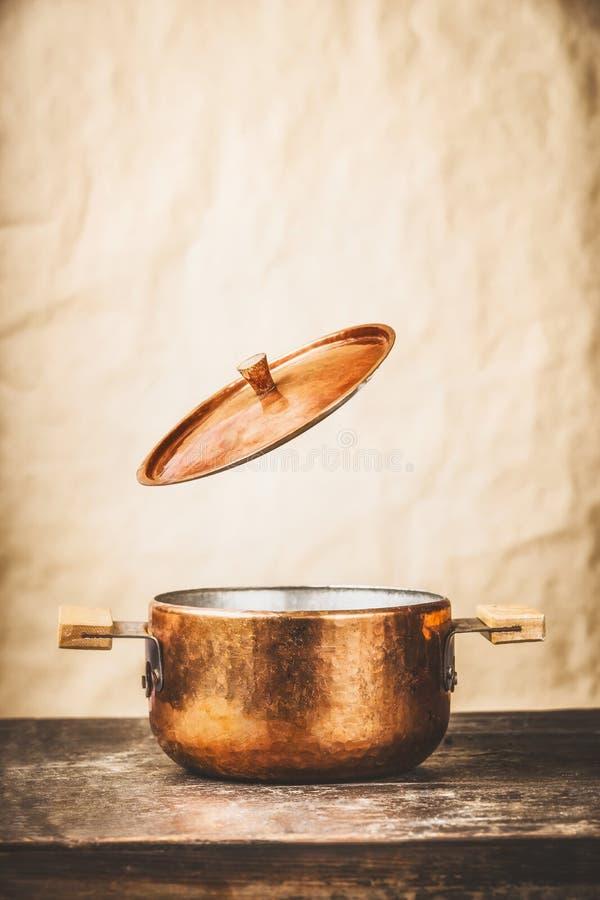 Vaso di cottura di rame con il coperchio aperto di volo sul tavolo da cucina di legno al fondo della parete fotografia stock libera da diritti