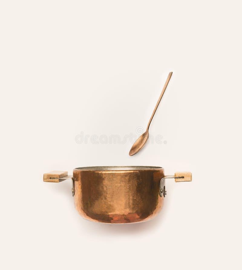 Vaso di cottura di rame con il cucchiaio su bianco fotografie stock