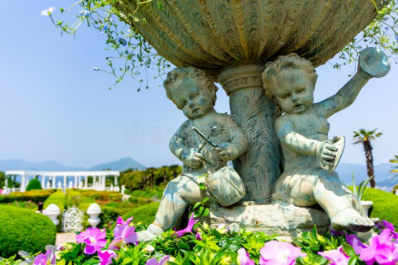 Vaso di fiore decorato con le sculture plaing childern di musica in giardino botanico sull'isola di Oedo Botania immagini stock