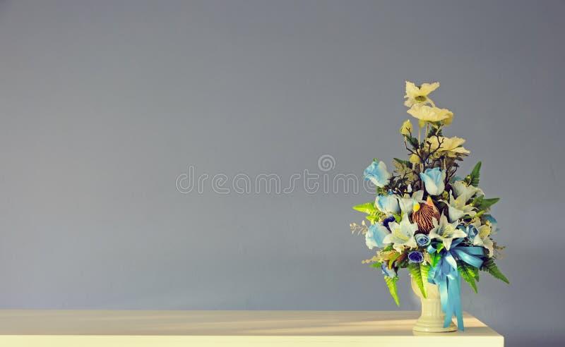 Vaso di fiori artificiali del mazzo sulla tavola dell'avorio con la parete grigia f fotografia stock